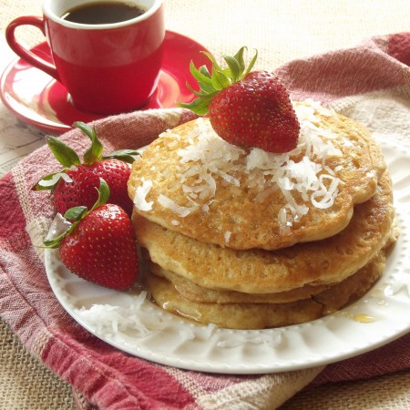 Stack of Quinoa Pancakes and Strawberries on a Plate with Coffee Cup in the Background