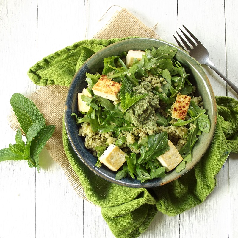 Overhead View of a Bowl of Couscous, Greens and Tofu on a Green Cloth with Fork on the Side