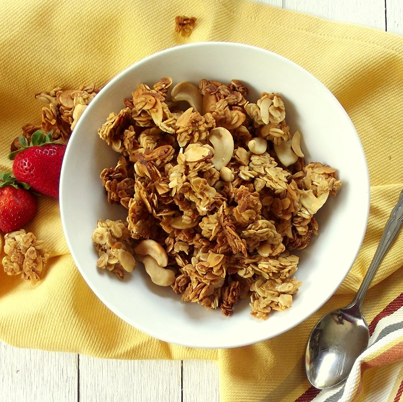Bowl of Granola on a Yellow Fabric Surrounded By Strawberries and Granola Clusters