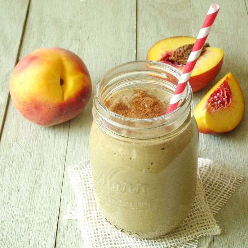 Peach Smoothie in a Jar with Peaches in the Background