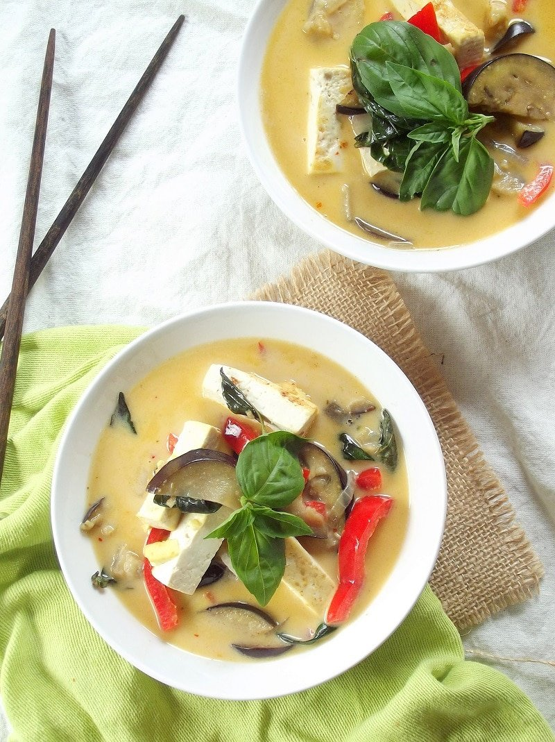 Two Bowls of Thai Red Curry with Tofu and Eggplant with Chopsticks and Napkin