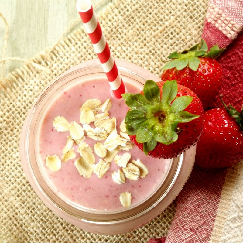 Overhead View of a Strawberry Smoothie in a Jar Topped with Oats, Surrounded by Strawberries