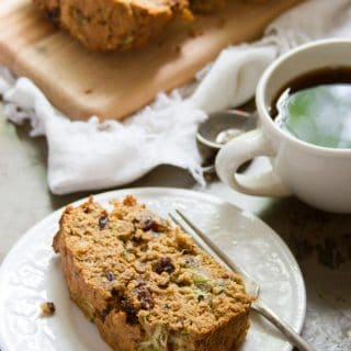 Slice of Vegan Zucchini Bread on a Plate with Coffee Cup in the Background