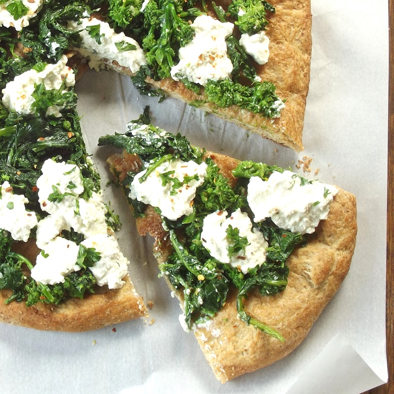 Overhead View of a Whole Vegan Broccoli Rabe Pizza with one Slice Cut Out