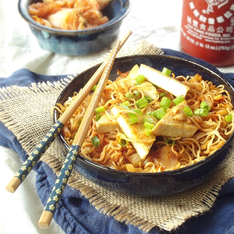 Bowl of Kimchi Ramen and Tofu With Chopsticks, Bottle of Sriracha in the Background