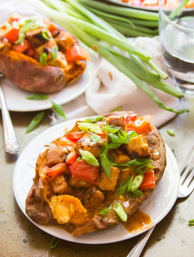 Two Ginger Tempeh Stuffed Sweet Potatoes with Almond Butter Sauce on Plates with Forks