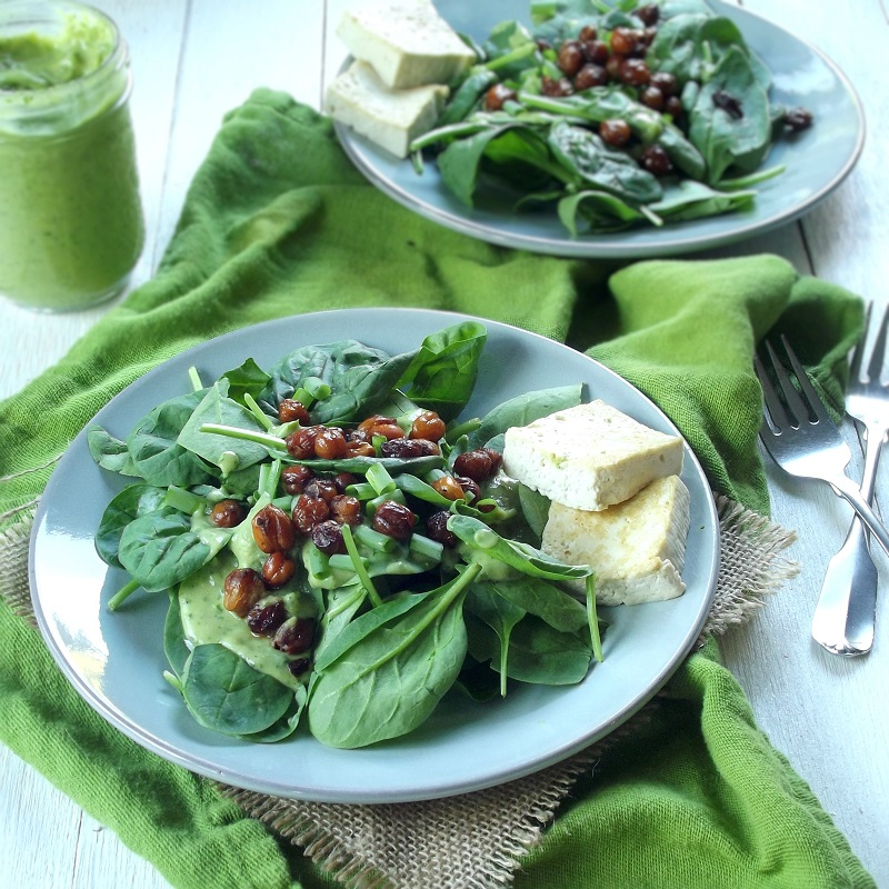 Two Plates of Vegan Spinach Salad with jar of Dressing and Forks on the Side