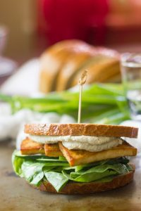 Smoky Baked Tofu Sandwich with Wasabi Cashew Mayo with Drinking Glass, Scallions and Bread in the Background
