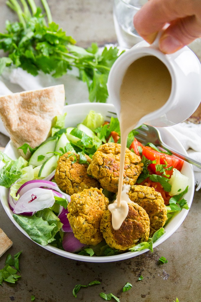 Pumpkin Falafel in a Bowl with Dressing Being Drizzled Over Top