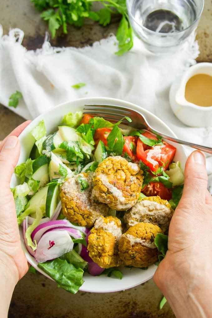 Hands Holding a Bowl Filled with Salad and Pumpkin Falafel