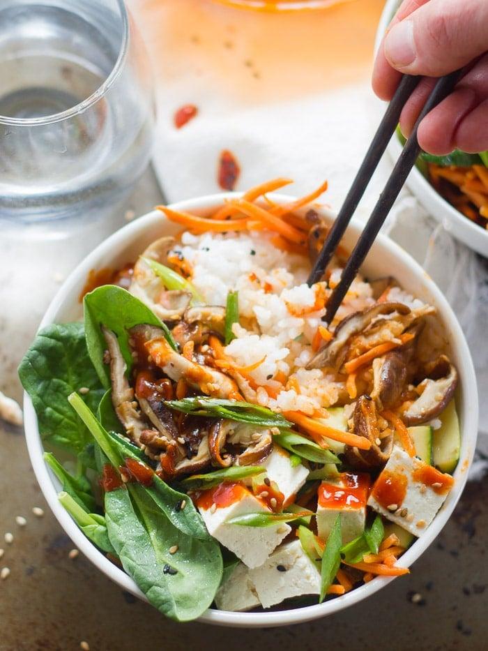 Hand Plunging a Pair of Chopsticks into a Bowl of Tofu Bibimbap
