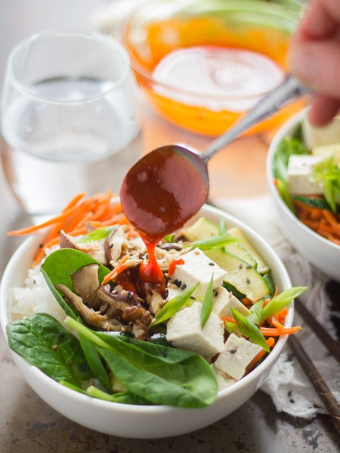 Spoon Drizzling Sauce Over a Bowl of Vegan Bibimbap