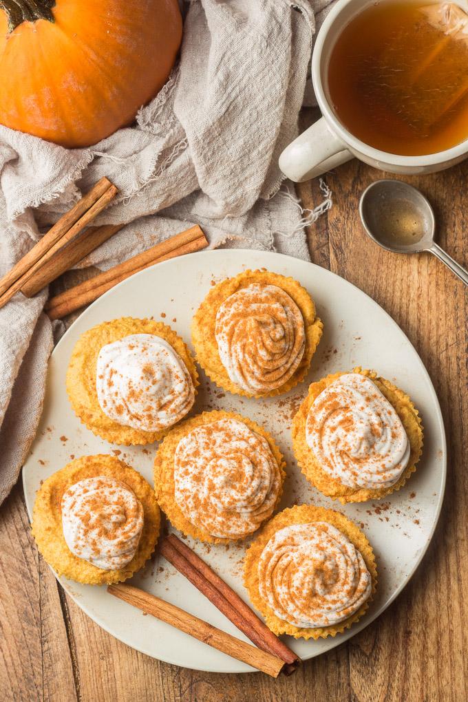 Table Set with a Plate of Mini Vegan Pumpkin Cheesecakes, Tea Cup, Napkin, and Pumpkin