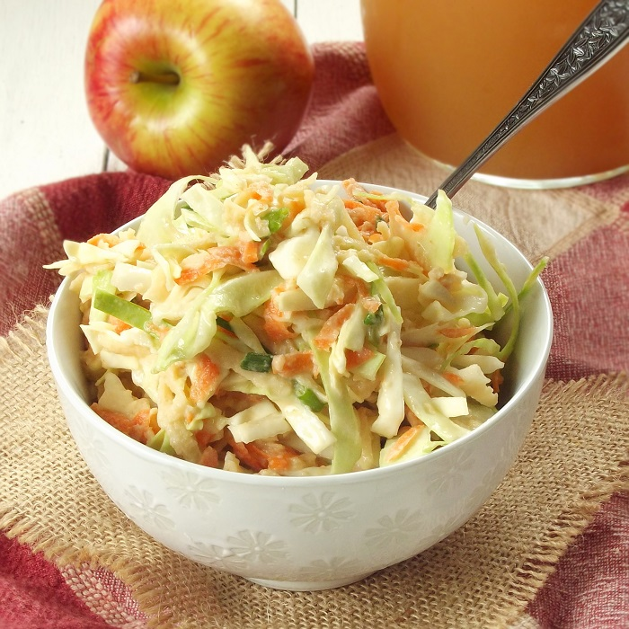 Bowl of Slaw with Spoon, Apple and Pitcher of Cider in the Background
