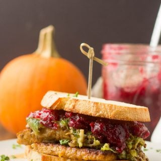 Vegan Thanksgiving Sandwich on a Plate with Pumpkin and Jar of Cranberry Sauce in the Background