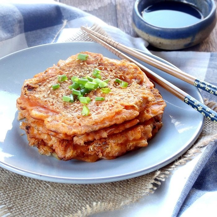 Stack of Kimchi Pancakes on a Plate with Scallions and Chopsticks, Dish of Sauce in the Background