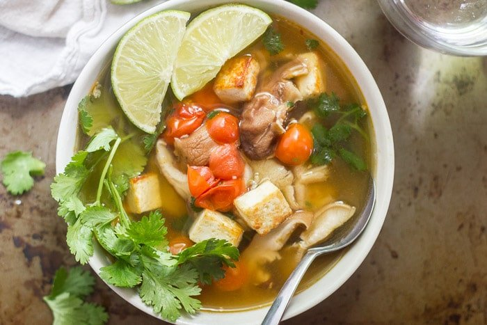 Bowl of Thai Lemongrass Soup with Spoon and Lime Wedges