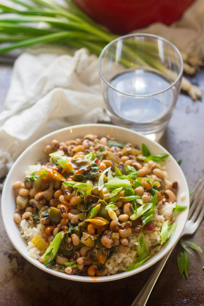 Bowl of Vegan Hoppin' John with Scallions and Water Glass in the Background