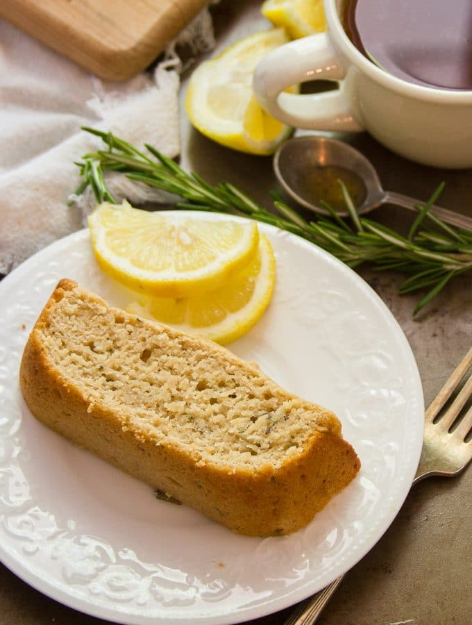 Slice of Rosemary Lemon Vegan Pound Cake on a Plate with Fork, Coffee Cup, Rosemary and Lemon Wedges in the Background