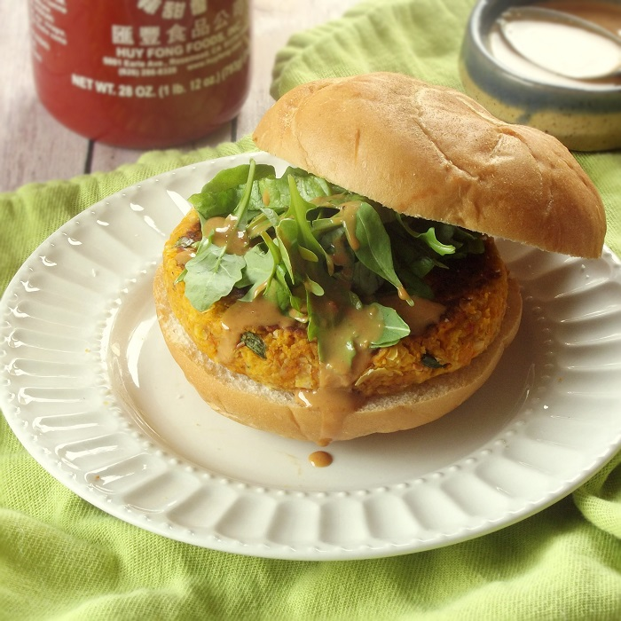 Vegan Massaman Curry Burger Dripping with Peanut Sauce on a Plate with Bowl of Sauce and Sriracha Bottle in the Background