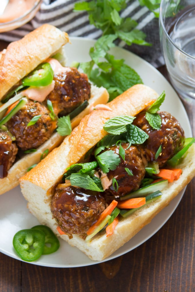 Close Up of a Vegan Meatball Banh Mi on a Plate with Drinking Glass in the Background