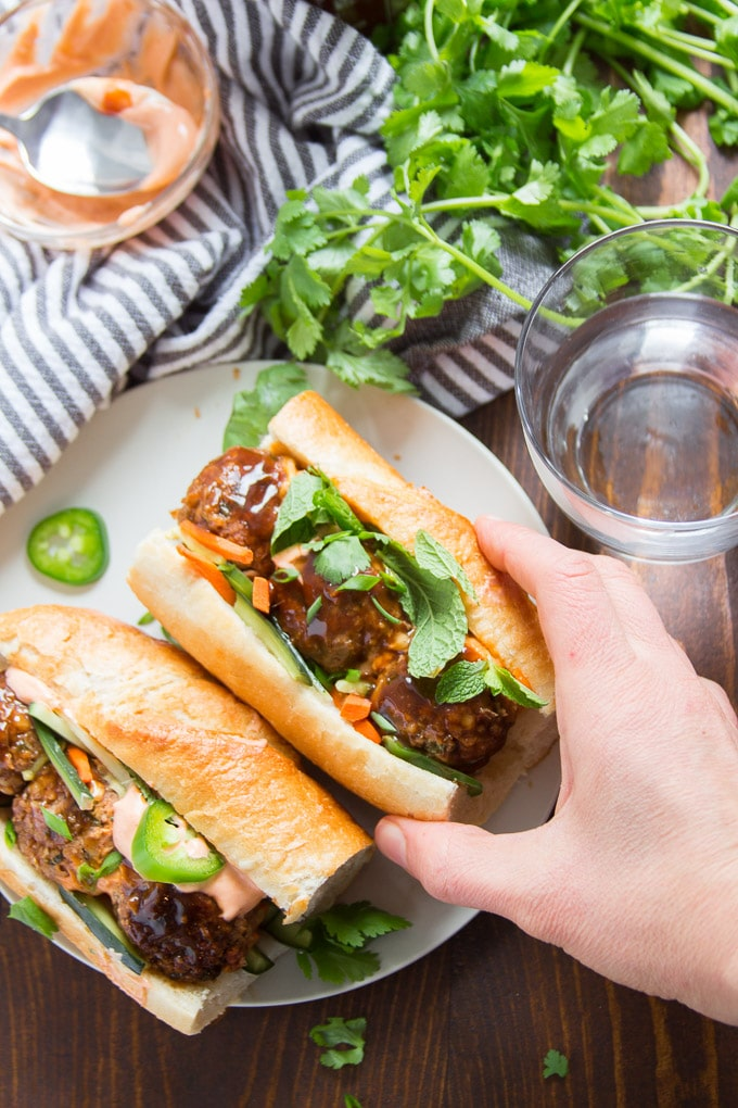 Hand Grabbing a Vegan Meatball Banh Mi From a Plate
