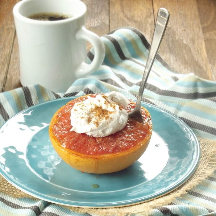 Half of a Broiled Grapefruit Topped with Coconut Whipped Cream on a Plate with Spoon, Coffee Cup in the Background