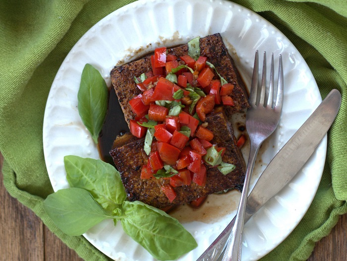 Overhead View of Two Balsamic Tofu Steaks Topped with Red Peppers and Basil on a Plate