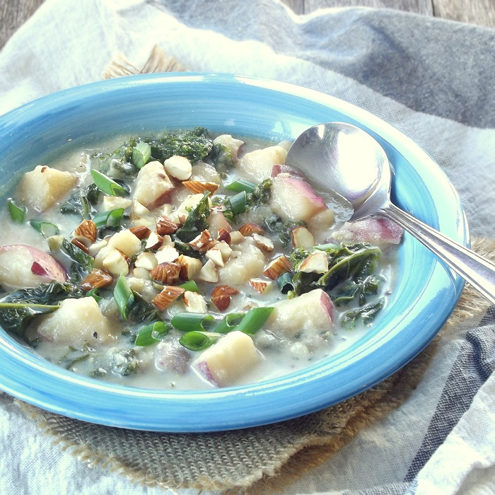 Bowl of Vegan Potato Kale Soup with Spoon
