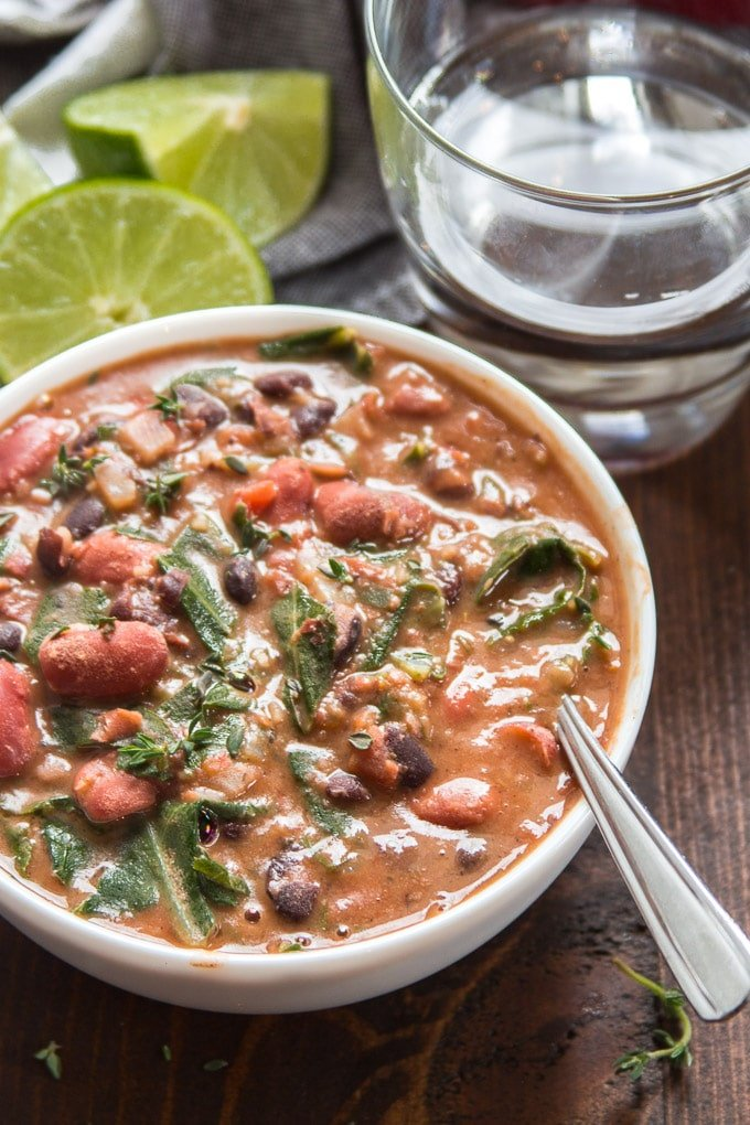 A Bowl of Caribbean Bean Soup with Collard Greens with Water Glass and Lime Half in the Background