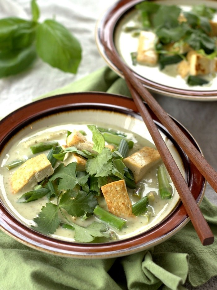 Two Bowls of Vegan Green Curry with Tofu & Veggies with Chopsticks and Basil in the Background