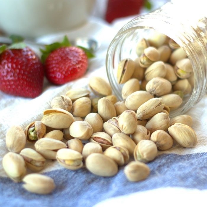Jar of Pistachios Spilling on a Blue and White Fabric, Strawberries in the Background