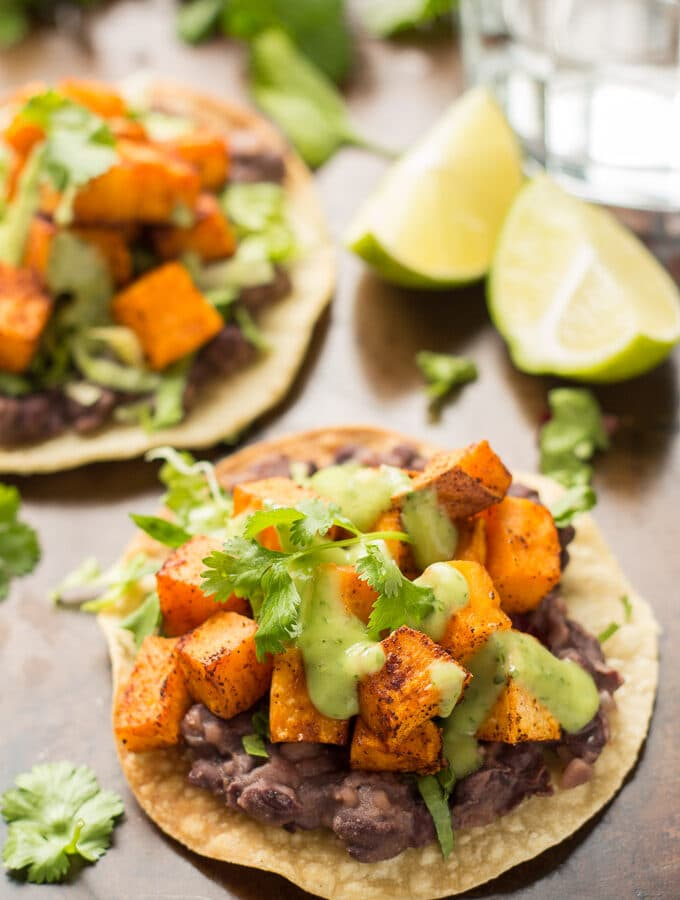 Two Sweet Potato Tostadas and Lime Wedges on a Baking Sheet