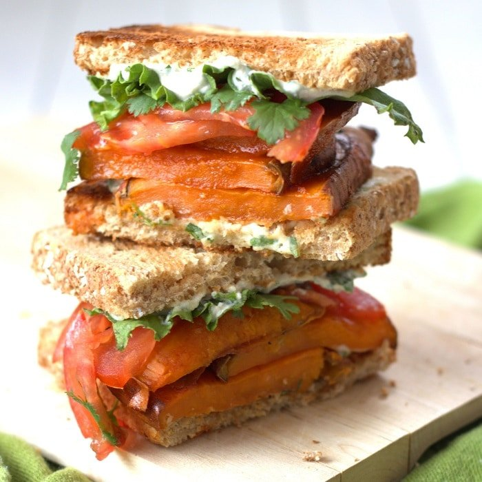 Two Halves of a Sweet Potato Sandwich Stacked on a Cutting Board