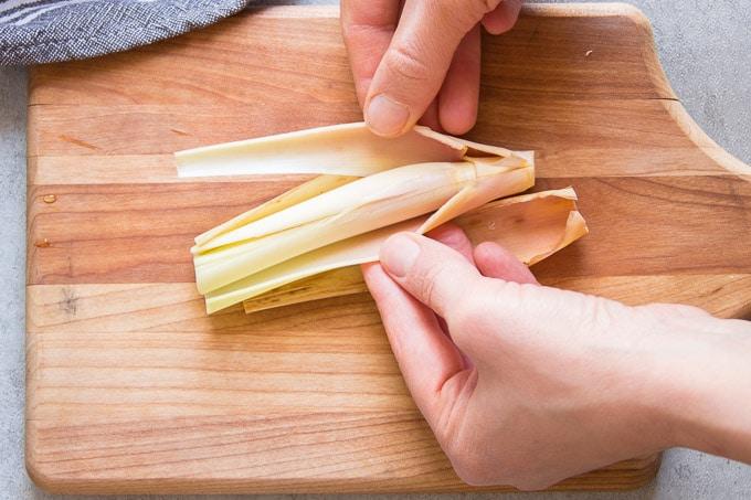 Hands Peeling Outer Sheath from a Lemongrass Stalk