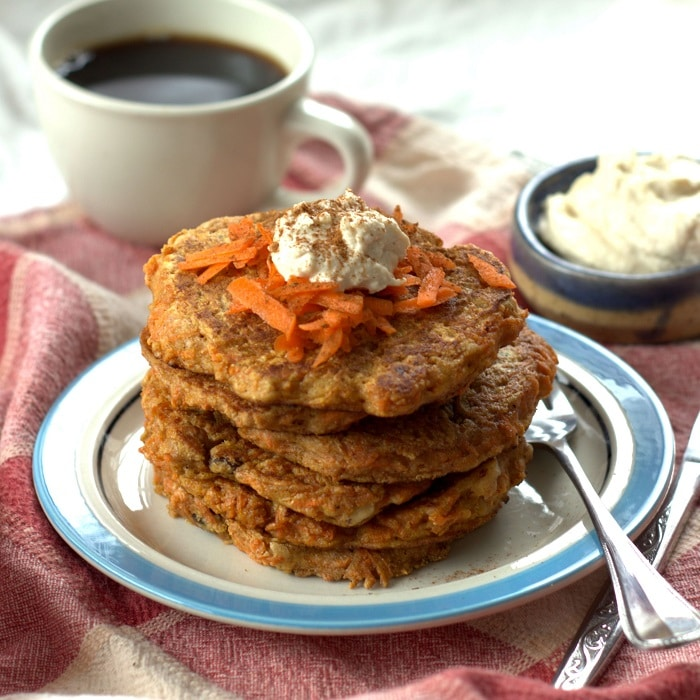 Stack of Carrot Cake Pancakes on a Plate with Fork, Coffee Cup and Bowl of Cream Cheese Maple Topping in the Background