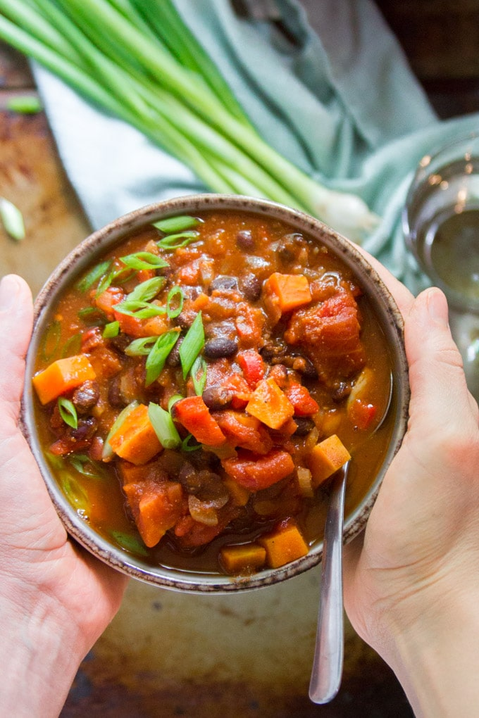 Hands Holding a Bowl of Chipotle Black Bean Sweet Potato Chili
