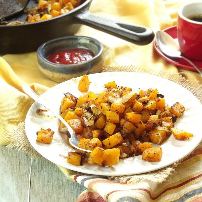 Butternut Squash Home Fries on a Plate with Skillet and Coffee Cup in the Background