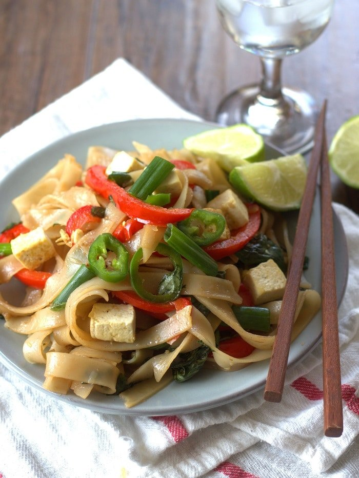 Plate of Five Spice Drunken Noodles with Chopsticks, Water Glass and Lime Slices