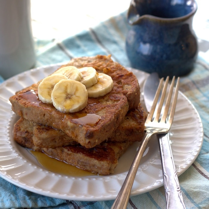 Vegan Peanut Butter Banana French Toast on a Plate with Fork, Knife, and Banana Slices on Top