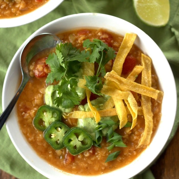 Overhead View of a Bowl or Red Lentil Taco Soup Topped with Avocado Cream, Tortilla Strips, Jalapeno Slices and Cilantro