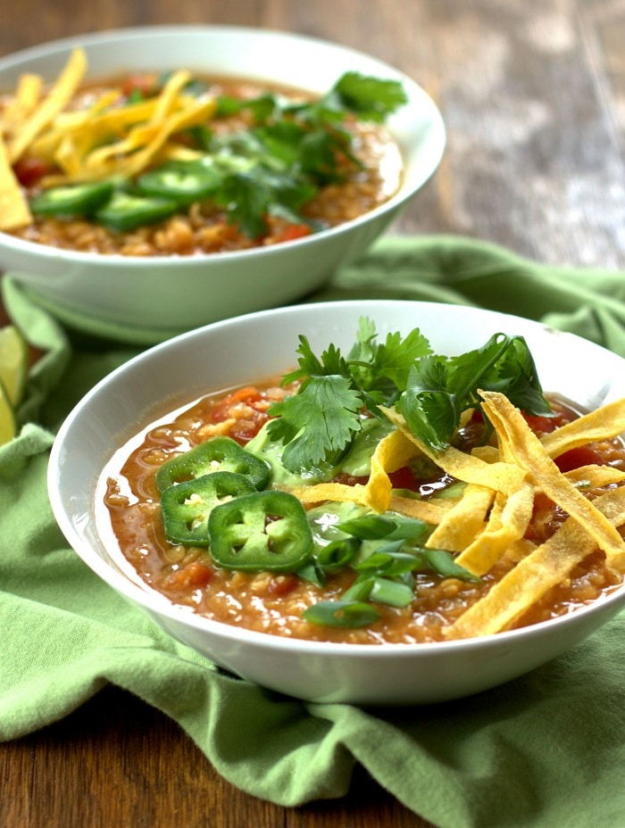 Two Bowls of Red Lentil Taco Soup Sitting on Green Fabric