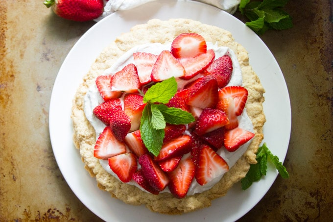 Overhead View of a Whole Vegan Strawberry Shortcake on a Plate Topped with Mint Leaves