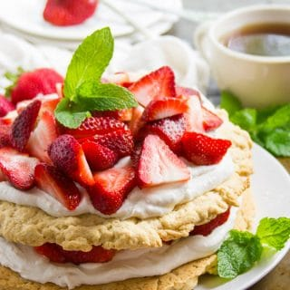 Vegan Strawberry Shortcake with Maple Ginger Strawberries on a Plate with Tea Cup and Plates in the Background