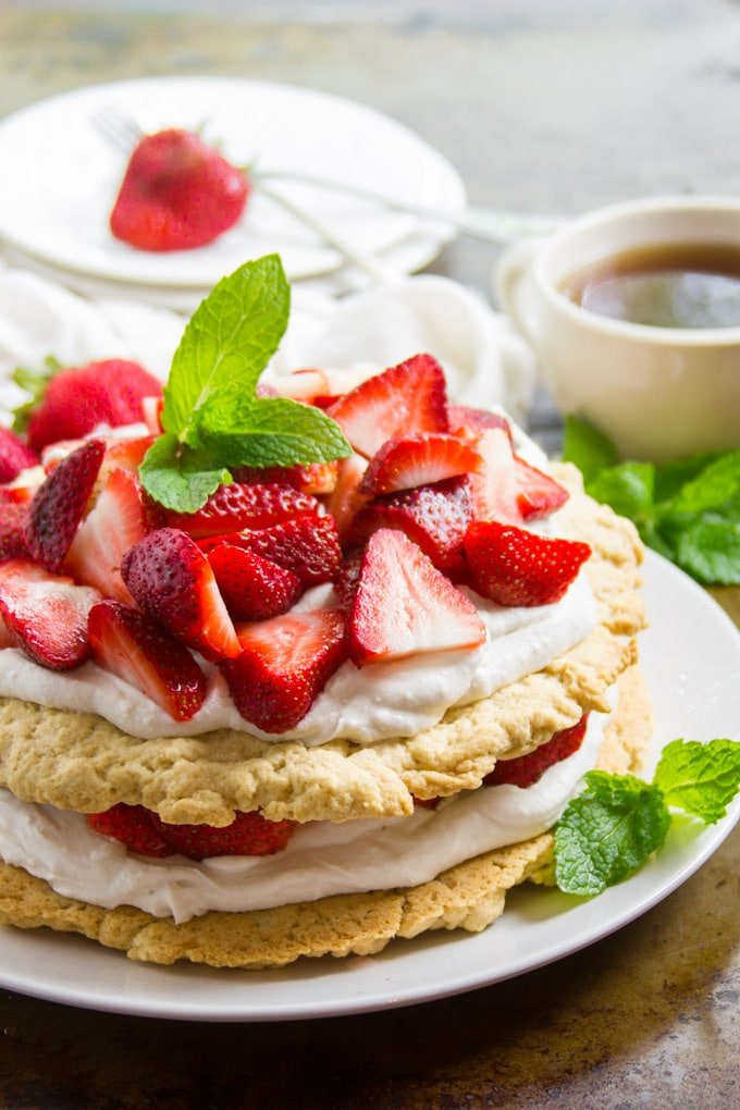Whole Vegan Strawberry Shortcake on a Plate with Tea Cup and Stack of Dishes in the Background