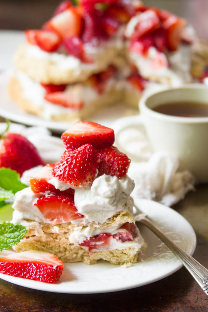 Slice of Vegan Strawberry Shortcake on a Plate with Tea Cup in the Background