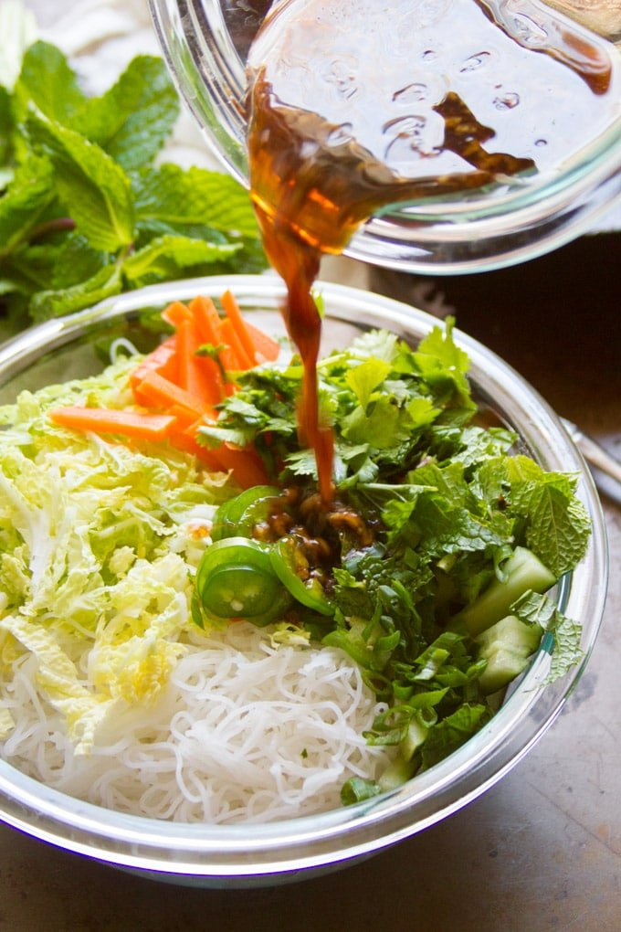 Dressing Being Poured Over a Bowl of Ingredients for Vietnamese Noodle Salad