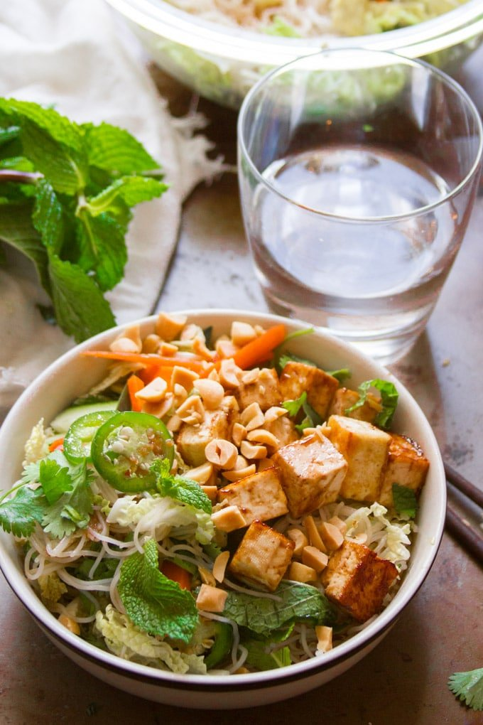 Bowl of Vietnamese Rice Noodle Salad with Hoisin Glazed Tofu with A Bunch of Mint and Drinking Glass in the Background