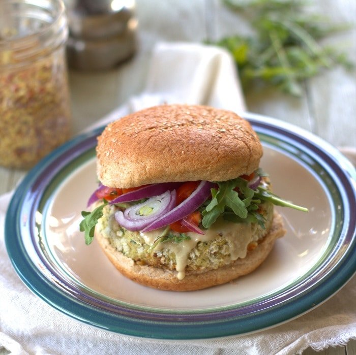White Bean Artichoke Burger on a Plate with Jar of Mustard and Greens in the Background