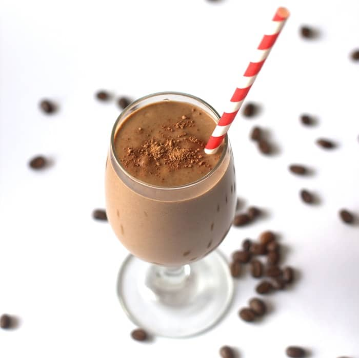 Mexican Chocolate Smoothie in a Glass Surrounded By Scattered Coffee Beans